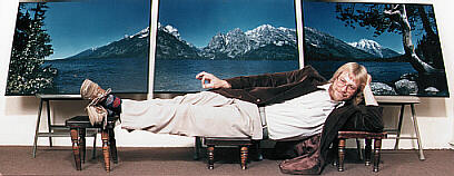 RL reclines in front of a large triptych of the Tetons.